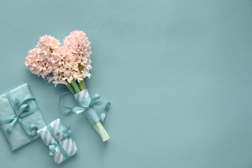Springtime turquoise background with hyacinth and gift boxes wrapped in stripy paper on paper background with copy-space