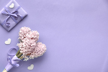 Springtime lilac colored background with pink hyacinth and wrapped gift box, copy-space