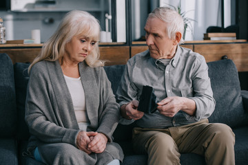 sad senior couple sitting on couch and holding wallets at home