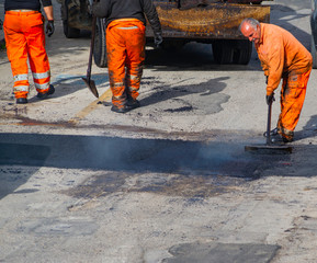 Worker regulate laying new asphalt to patch a bump in the road.