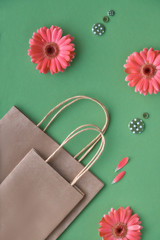 Coral gerbera daisy flowers and craft papper shopping bags on green paper background, copy-space