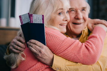 smiling senior couple hugging and holding air tickets with passports at home