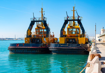 Two tugs boat stands ready to help ships in the port of Bari
