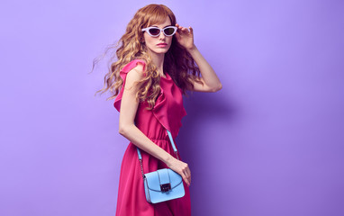 Wall Mural - Fashion. Gorgeous woman in summer Trendy dress, glamour makeup posing in Studio. Enchanting beautiful fashionable model girl with Stylish handbag, accessories, make up on purple