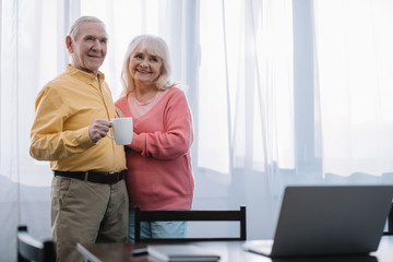 selective focus of smiling senior couple in casual clothes holding cup of coffee at home with copy space