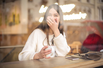 Girl sitting in a cafe, laughing a lot