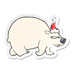 distressed sticker cartoon of a angry polar bear wearing santa hat