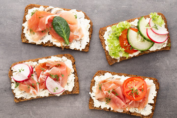 Sandwich with cereals bread and salami on dark marble background.