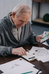 senior man sitting at table with paperwork and using calculator while counting money at home