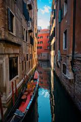 Narrow canal with gondola in Venice, Italy