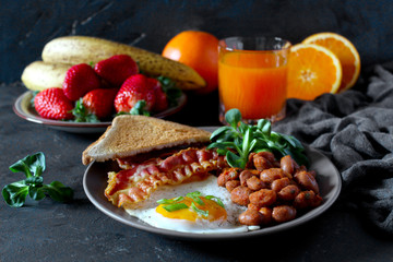 English breakfast with eggs, bacon, beans, toasts, fresh juice and fresh fruits. Top view with copy space.