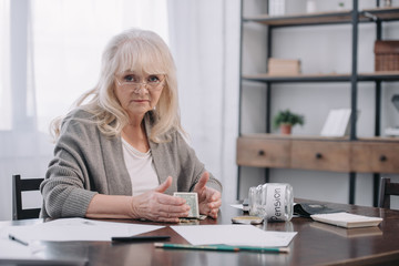 senior woman sitting at table with money, paperwork and empty glass jar with 'pension' word