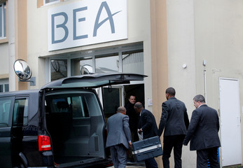 Men unload a case from a diplomatic car of the Ethiopian Embassy arrives at the headquarters of France's BEA air accident investigation agency in Le Bourget