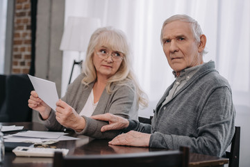 senior couple in casual clothes holding bills while sitting at table