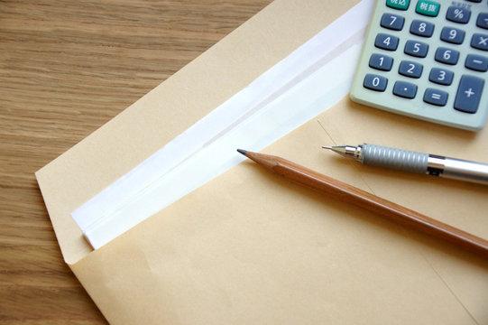 A4の茶封筒に入った書類と電卓とペン