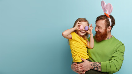 Look forward to celebrating Easter. Lovely family of daughter and father have eggs hunt, glad spring is coming. Satisfied red haired man carries little child who covers ears with colored eggs