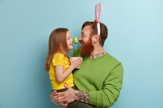 Lovely family play together, keep noses together on green Easter egg, enjoy pleasant moments of preparation to spring Christian holiday. Lovely female child in yellow t shirt spends time with father