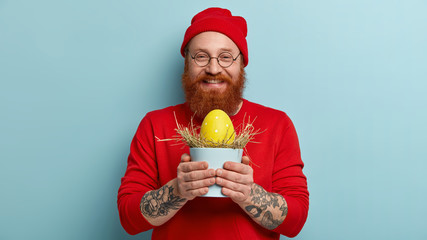 Look at my first decorated Easter egg. Smiling redhead satisfied man carries pot with hay and yellow egg, wears red clothes, ready to hide in garden for children, isolated over blue background