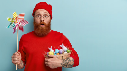 Easter celebration concept. Stupefied man with foxy stubble, carries basket with dyed eggs on hay, holds paper windmill, shocked to find out religious rules during fixed feast, models indoor