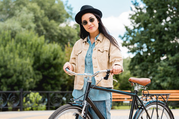 happy girl in sunglasses and hat standing with bicycle in park