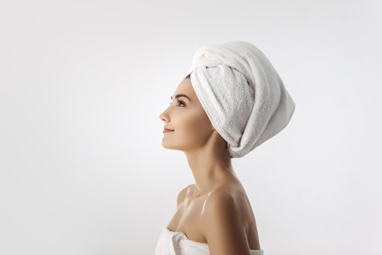 Beautiful young woman in towel after bath on white background