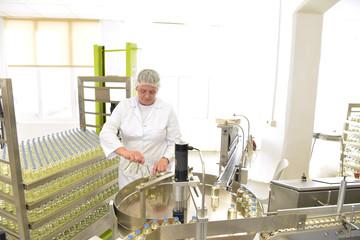 Frau in der Pharmaindustrie - Abfüllanlage von Medizin am Fliessband // Woman in the pharmaceutical industry - Filling line for medicine on an assembly line