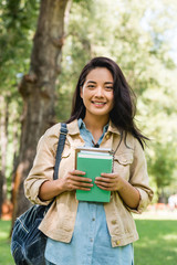 happy young woman holding books and smiling in park