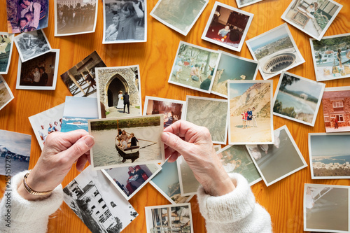 Wall mural Top view of a senior caucasian woman looking at an old photos themes of memories nostalgia photos retired