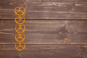 Group of five whole mini salted pretzels flatlay on brown wood