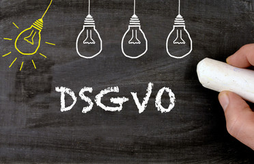 Hand writing DSGVO with bulbs on blackboard