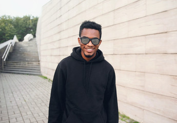 Wall Mural - Portrait happy smiling african man in black hoodie, sunglasses on city street over gray brick wall background
