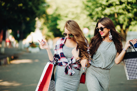 Beautiful smiling girls walking at park after shooping and big sales with many papers bags in hands. Women in glasses with red lips, fashionable wearing in dresses and sunglasses. Summertime.