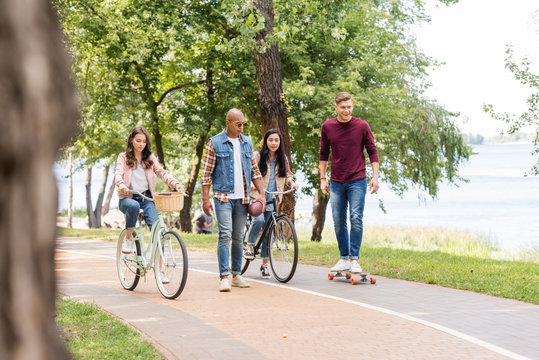 Multiethnic friends riding bikes, long board, and walking in park