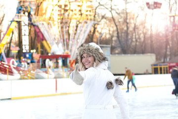 Charming smiling young woman in a ski suit. Beautiful blond girl in a white suit on a ski rink.