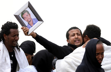 A relative holds a portrait as he mourns at the scene of the Ethiopian Airlines Flight ET 302 plane crash, near the town Bishoftu