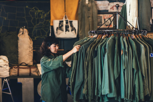 Pretty Asian woman standing by the clothes rack at vintage military shop and folding shirts.