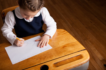 Little Girl Writing While Sitting in Old School Desk - Education