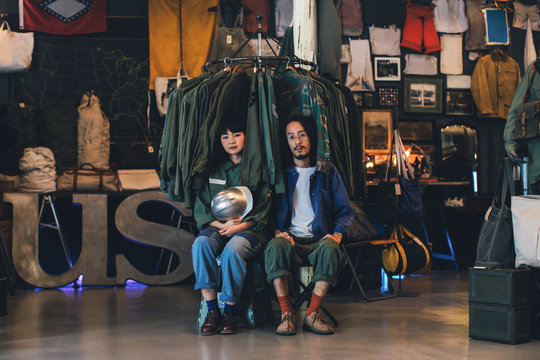 Portrait of Asian couple sitting at vintage military shop and looking at camera.