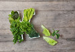 Vitamin K in food concept. Plate in the shape of the letter K with different fresh leafy green vegetables, lettuce, herbs on wooden background. Flat lay or top view