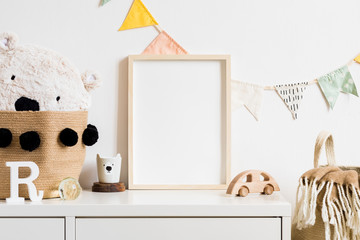 Stylish scandinavian nursery interior with  white teddy bear, wooden toys and cup. Hanging cotton flags. Natural basket on the white background wall. Cozy and sunny childroom. Real photo. Template.