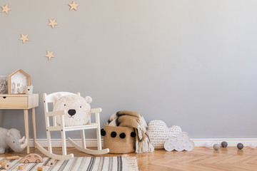 Stylish scandinavian newborn baby room with toys, teddy bear on children's chair, natural basket with blanket. Modern interior with grey background walls, wooden parquet and stars pattern. Real photo.