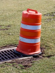A close view of the orange and white traffic barrel.