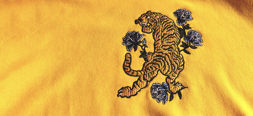 Tiger embroidery on a yellow sweatshirt.