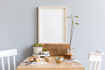 Stylish and modern interior design of kitchen space with small wooden table  with mock up photo frame, avocado plant, succulents, cups of tea and tasty dessert. Scandinavian space decor.