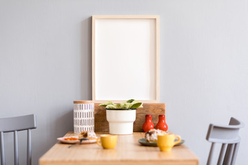 Stylish and modern interior of kitchen space with small wooden table  with mock up photo frame, beautiful plant, design cups and tasty dessert. Scandinavian room decor with kitchen accessories.