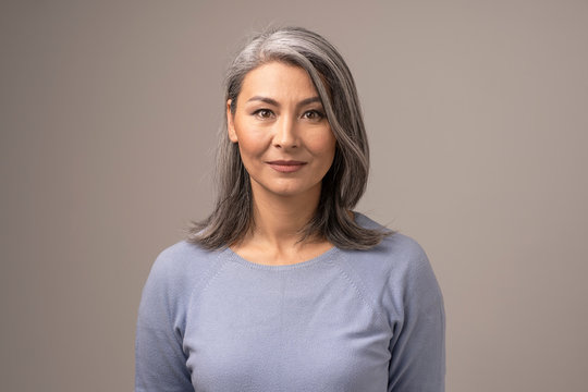 Beautiful Mongolian Woman with Gray Hair on a Gray Background.