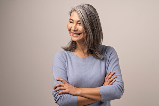 Smiling Asian senior woman with crossed arms