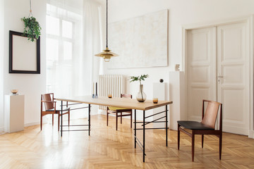 Sunny and elegant dining room interior with design sharing table, chairs, gold pedant lamp, abstract paintings and stylish accessories. Tropical leafs in vase. Eclectic decor. Brown wooden parquet.