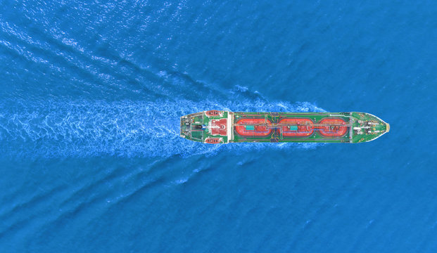 Aerial top view Ship tanker oil or gas LPG full speed with beautiful wave transportation from refinery on the sea.