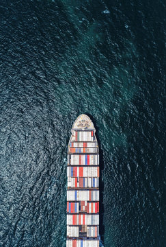 Aerial top view container ship full load container on the deep sea for logistic, import export, shipping or transportation.